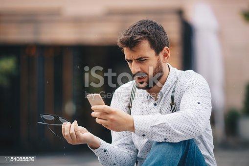 825083556istockphoto Man texting on phone 1154085526