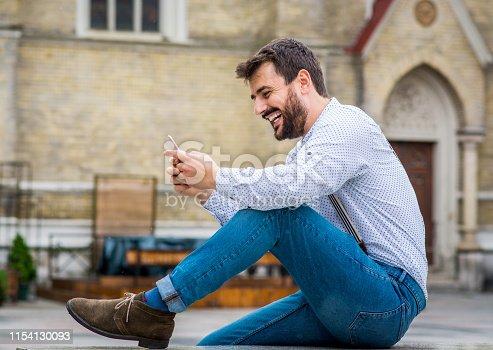 825083556istockphoto Man texting on phone 1154130093