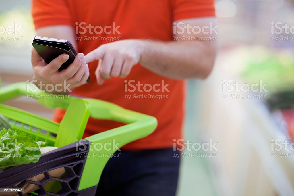 Man texting on smart phone while shopping for groceries stock photo