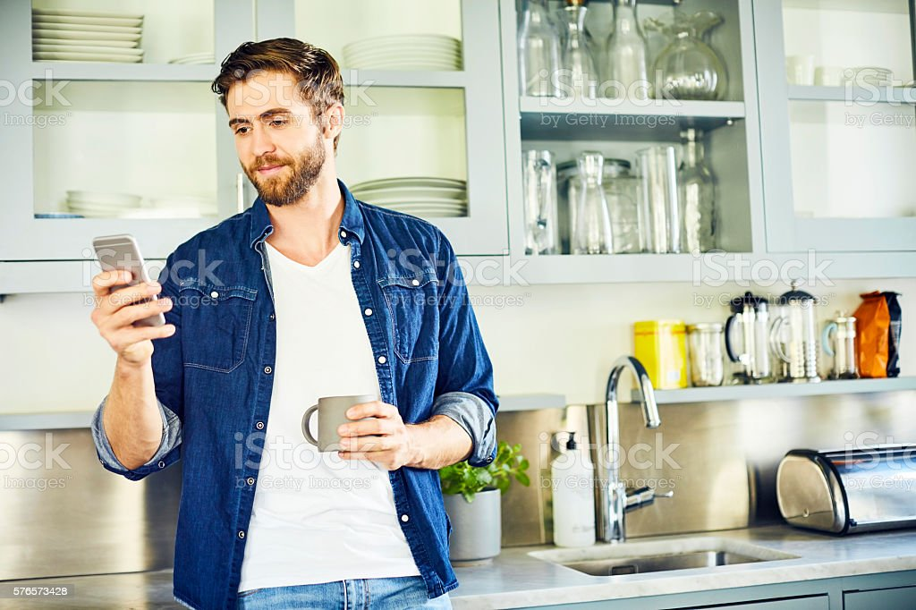 Man texting through smart phone while holding coffee cup – Foto