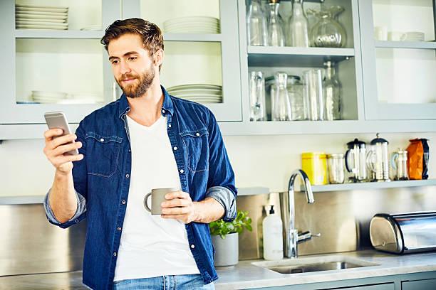 man texting through smart phone while holding coffee cup - telefonschrank stock-fotos und bilder