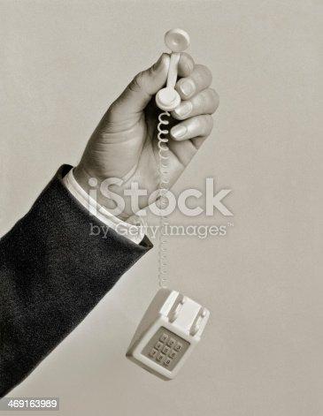 closeup of man with tiny toy phone