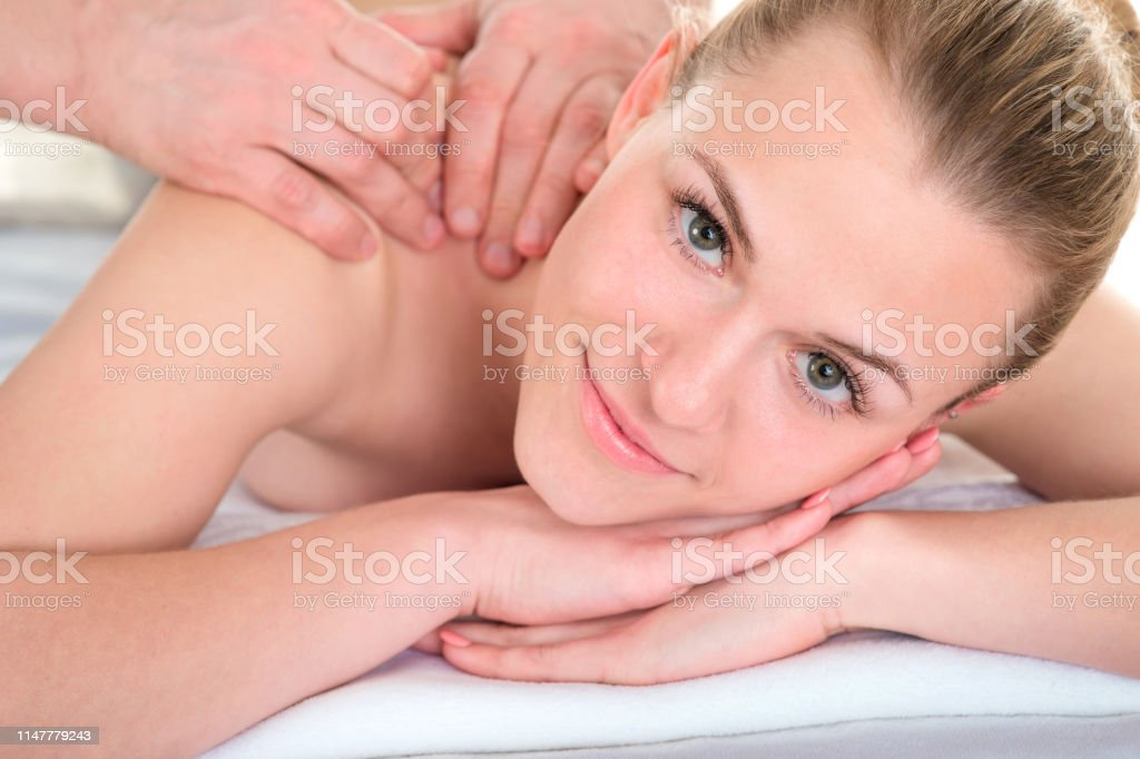Man therapist massaging female shoulder and arms. Relaxing spa...