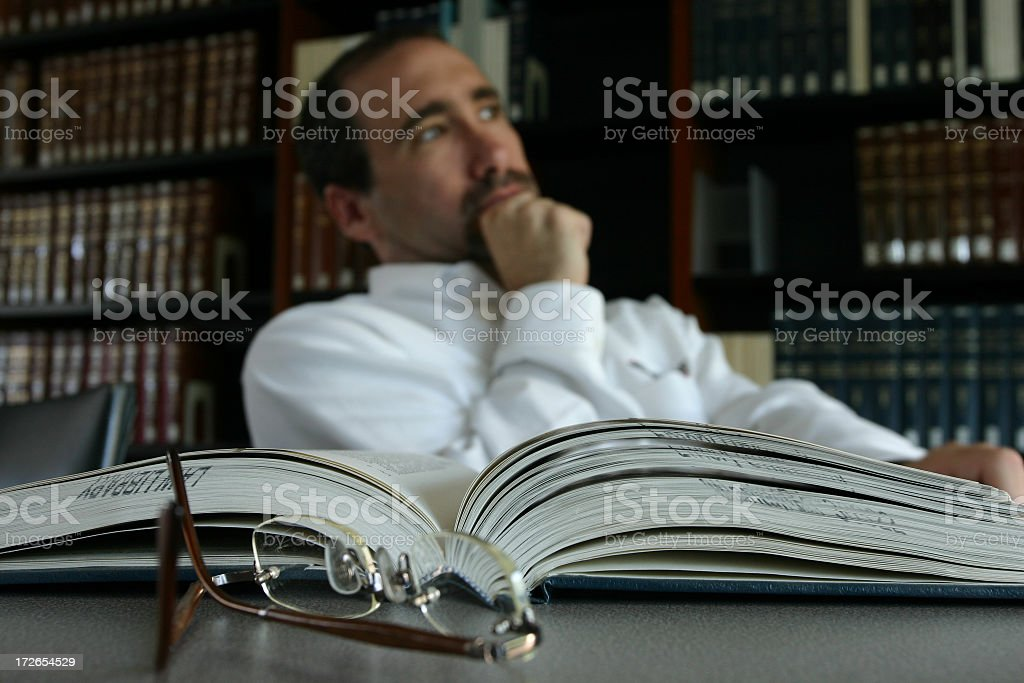 Man thinking at his desk by an open book in a library stock photo