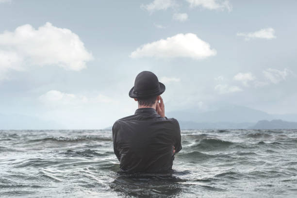 man thinking underwater observing clouds surreal concept stock photo