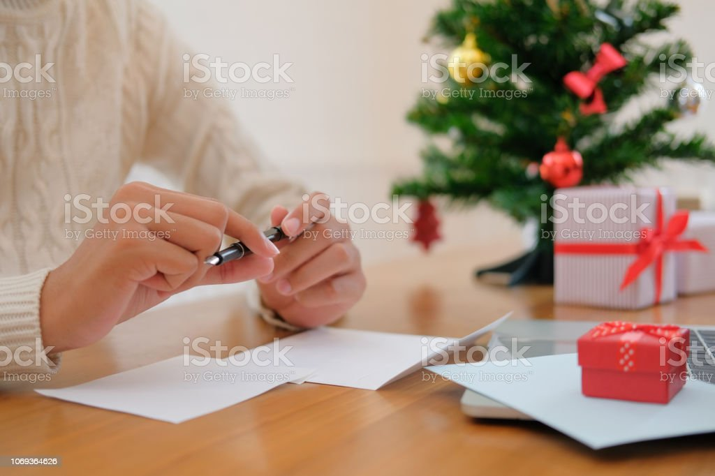 man wearing cream sweater thinking writing christmas letter greeting...