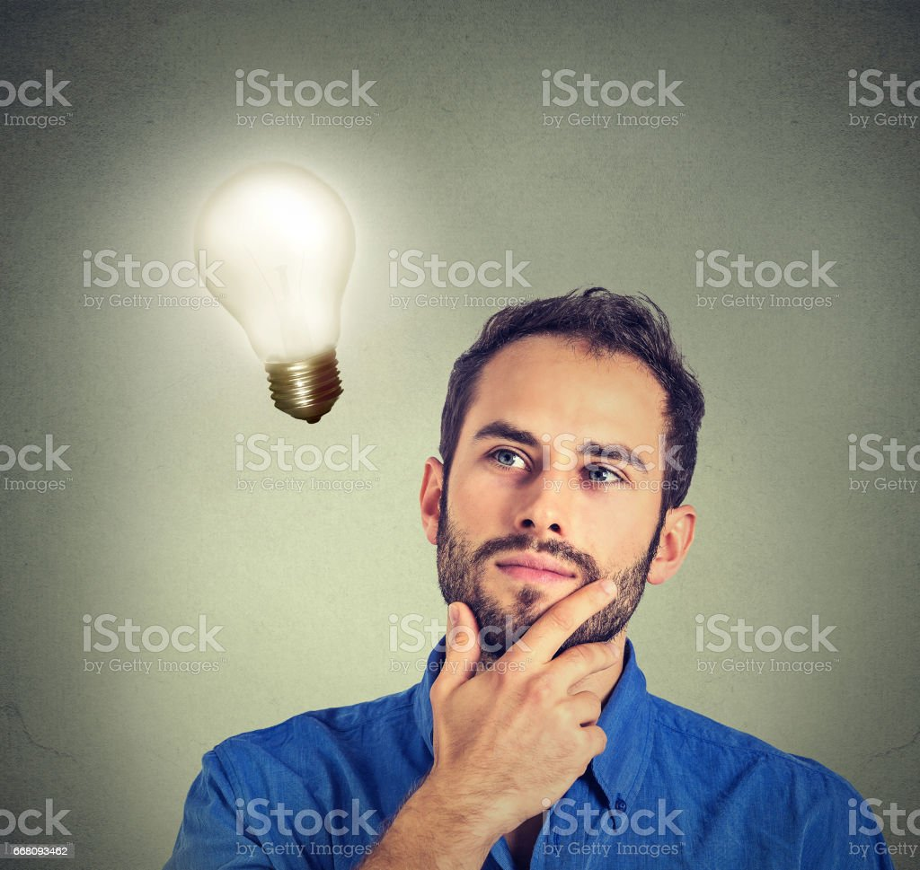 man thinks looking up at bright light bulb – zdjęcie