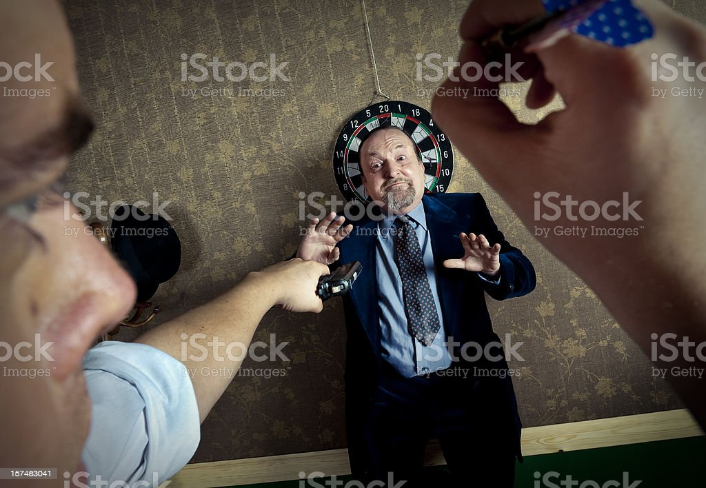Man threatened in a dartboard royalty-free stock photo