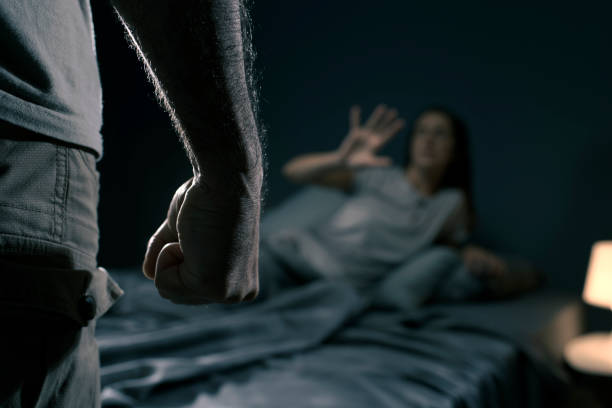 Man threatening a woman in the bedroom stock photo