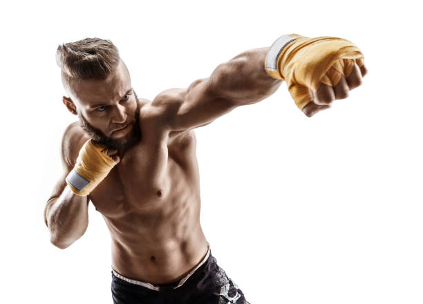 man throwing a fierce and powerful punch. - combat sport stock pictures, royalty-free photos & images