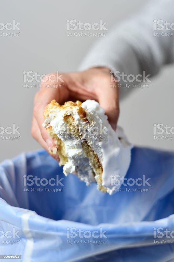 man throwing a piece of cake to the trash bin stock photo