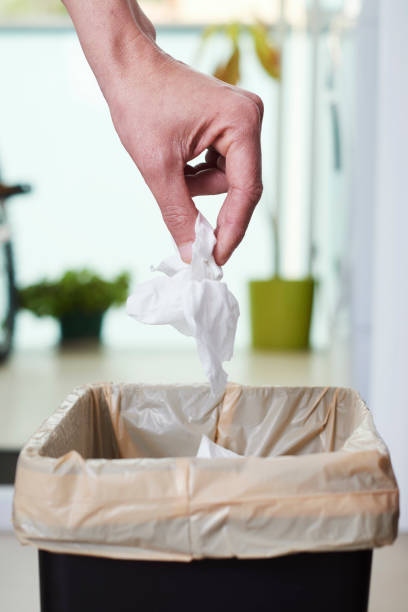 man throwing a used wet wipe to the trash bin stock photo