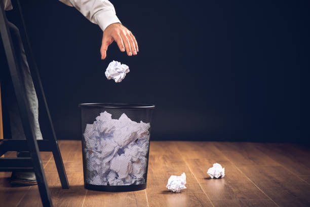Man Throwing Away Papers into Trash Bin, Inspiration, Creativity and Idea Concept For Business stock photo