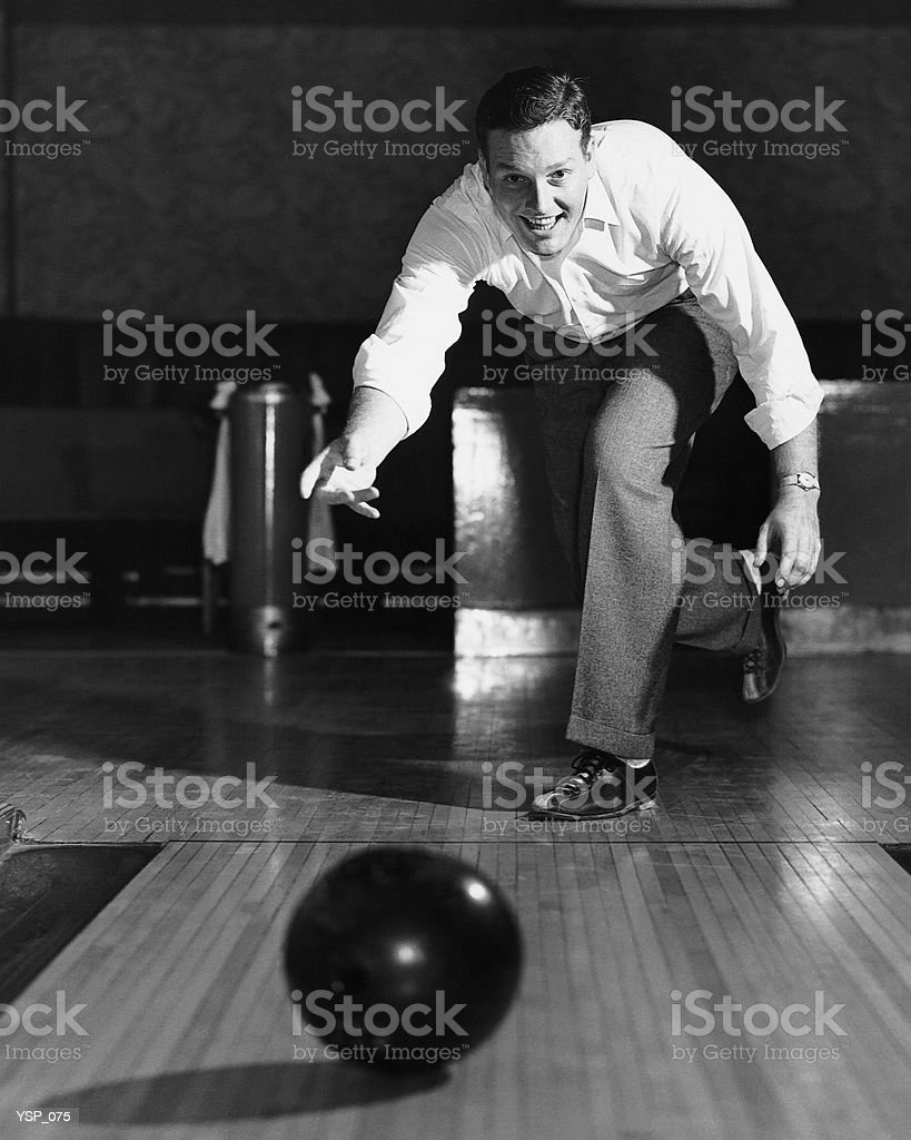 Man throwing bowling ball down lane royalty-free stock photo