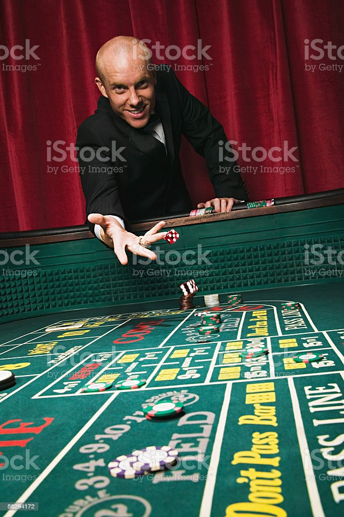 Man throwing dice at craps table stock photo