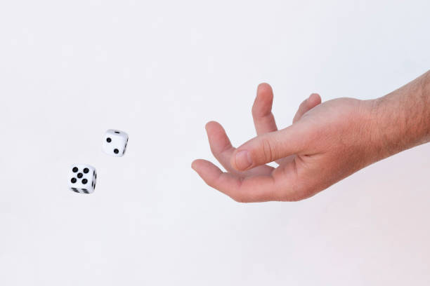 Man Throwing Dice a man throwing 2 dice with 2 and 5 showing jude beck stock pictures, royalty-free photos & images