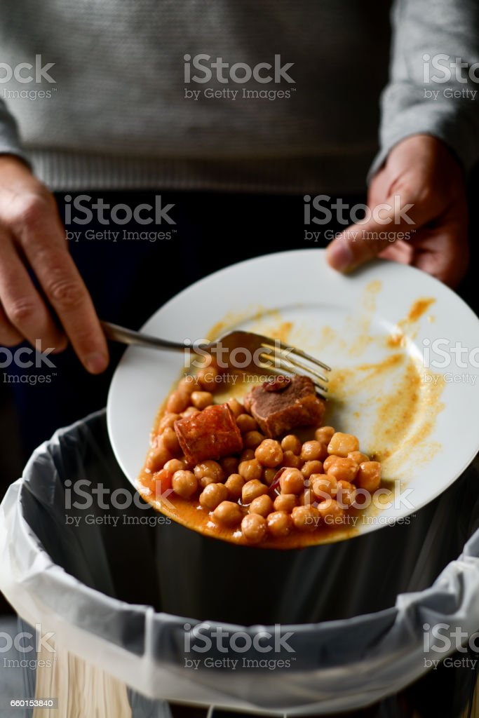man throwing leftovers to the trash bin stock photo