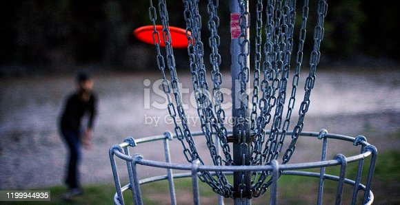 A Man Throws a Disc Golf Putter into a Disc Golf Basket in an Uncultivated Outdoor Area Next to the Colorado River at a Disc Golf Course at Sunset (Frisbee Golf)