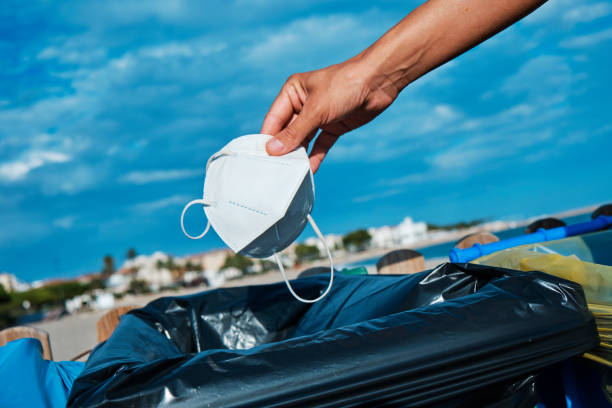 man throws used mask to the trash can on the beach stock photo