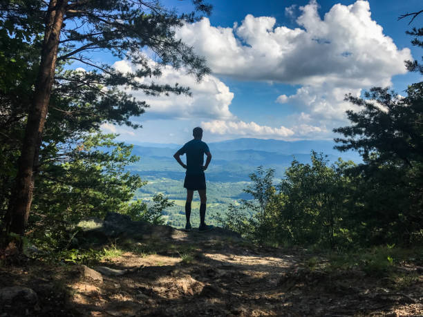 man thru-hiking appalachian trail a man stands on an overlook near great smoky mountains national park along the appalachian trail. appalachian trail stock pictures, royalty-free photos & images