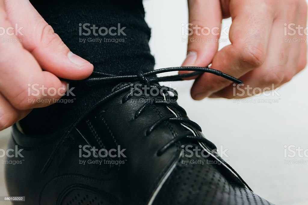 man ties the laces on his black shoes stock photo