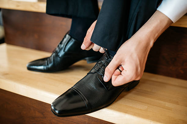 Man ties the laces on his  shoes stock photo