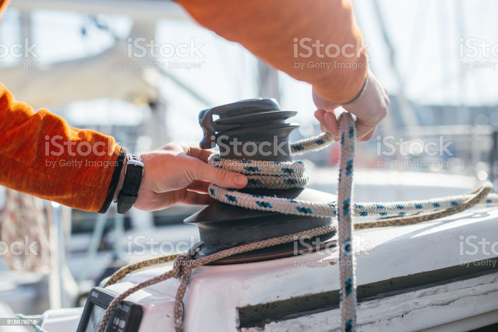 Man ties up nautical rope on winch on boat stock photo