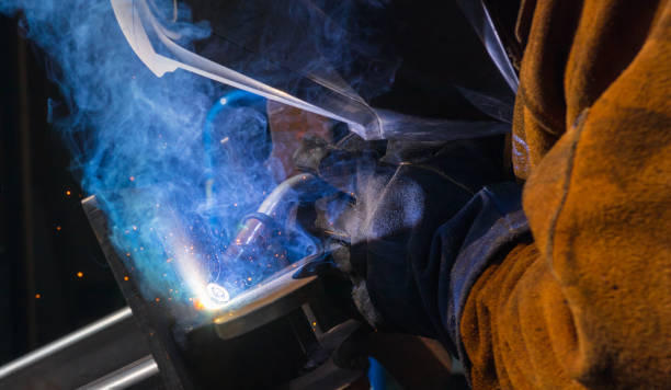 Man tig welding steel cast plates with brilliant bright white star burst bloom of lights stock photo