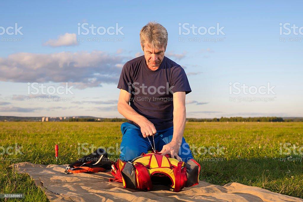 man tighten the valve of parachute  knapsack stock photo