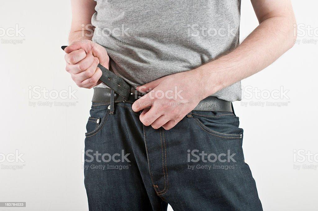 man tightening belt. stock photo