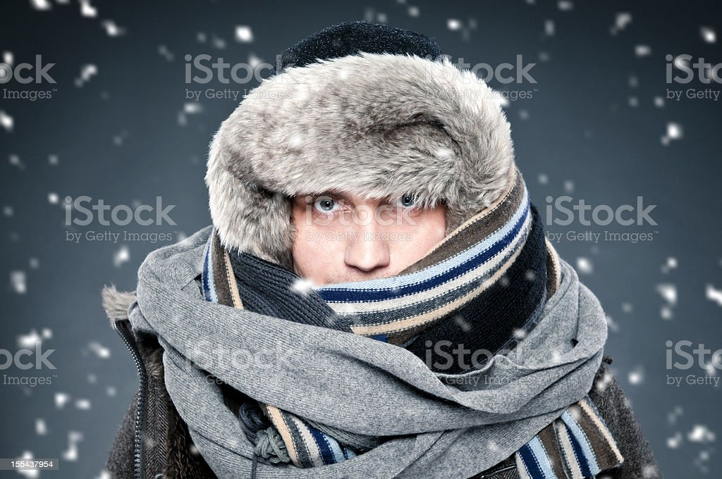 Man tightly bundled up in winter clothes, shawl, fur cap stock photo