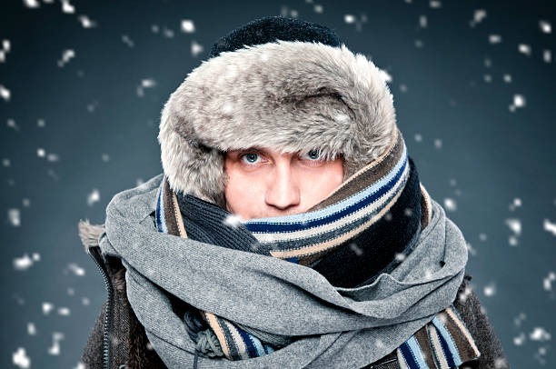 Man tightly bundled up in winter clothes, shawl, fur cap Close-up of handsome man tightly wrapped in winter clothes: shawl, cap. He has two scarves, thick warm fur cap. It is snowing, studio shot. bundle stock pictures, royalty-free photos & images