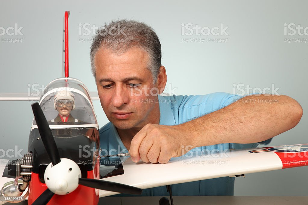 Man tinkering on large model airplane with miniature pilot stock photo