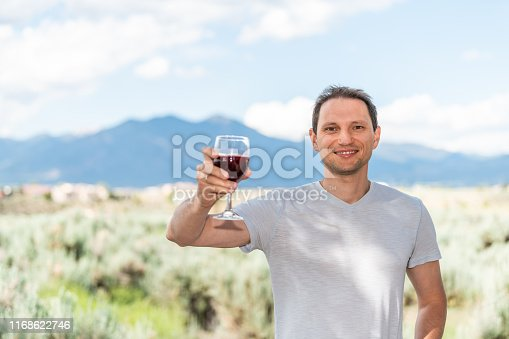 Man toasting red wine by view of Taos Sangre de Cristo mountains view from Ranchos de Taos valley bokeh background in backyard