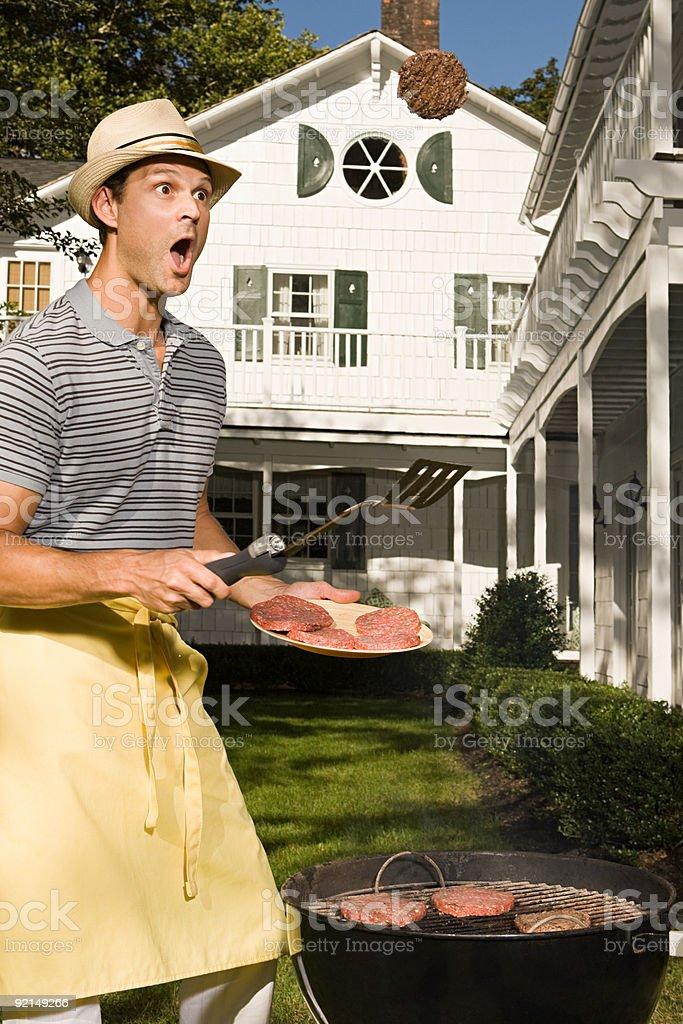 Un homme se retourner barbecue, hamburgers - Photo