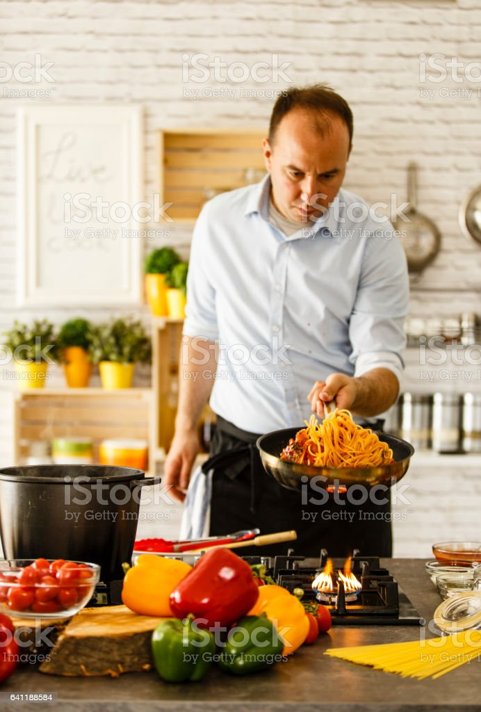 Man tossing pasta from frying pan stock photo