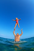 Grandfather tossing up the high air with water splashes joyful baby girl on sea beach. Outdoors child activity, active healthy lifestyle, swimming with fun on summer family vacation on tropical island.