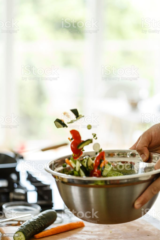 Man tossing vegetable salad stock photo
