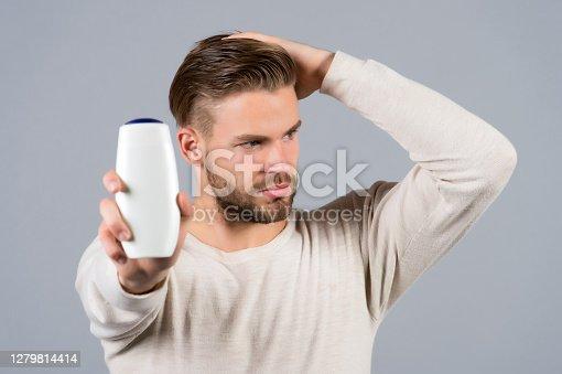 Man touch healthy hair with shampoo bottle in hand. Hair care, health, health care. Hygiene, grooming, beauty. Barber, hairdresser, salon.