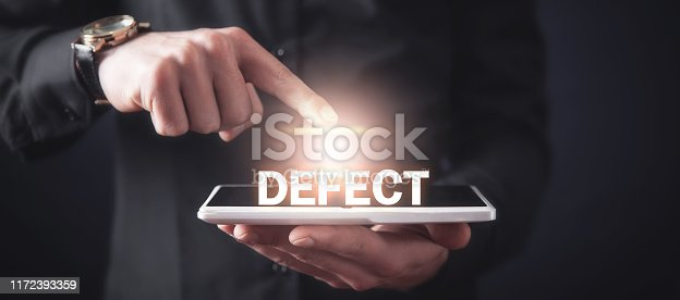 Man touching Defect word and using tablet computer.