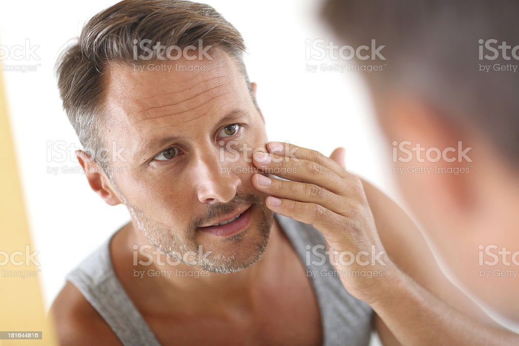 Man touching face in a bathroom mirror stock photo