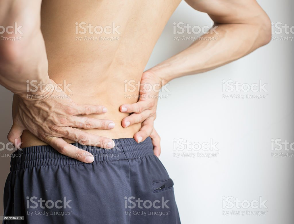 Man touching his back because of severe back pain stock photo
