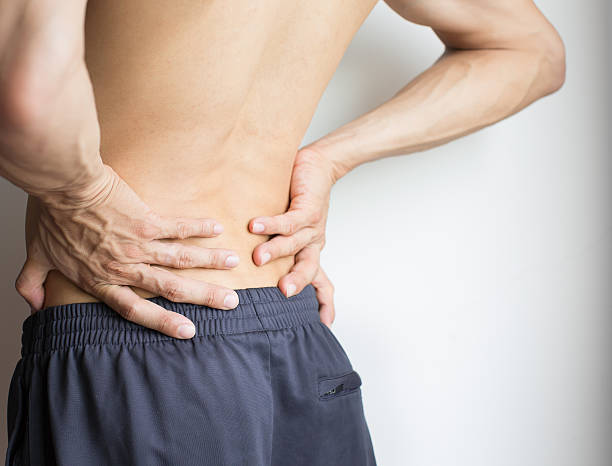 man touching his back because of severe back pain - low section stock photos and pictures
