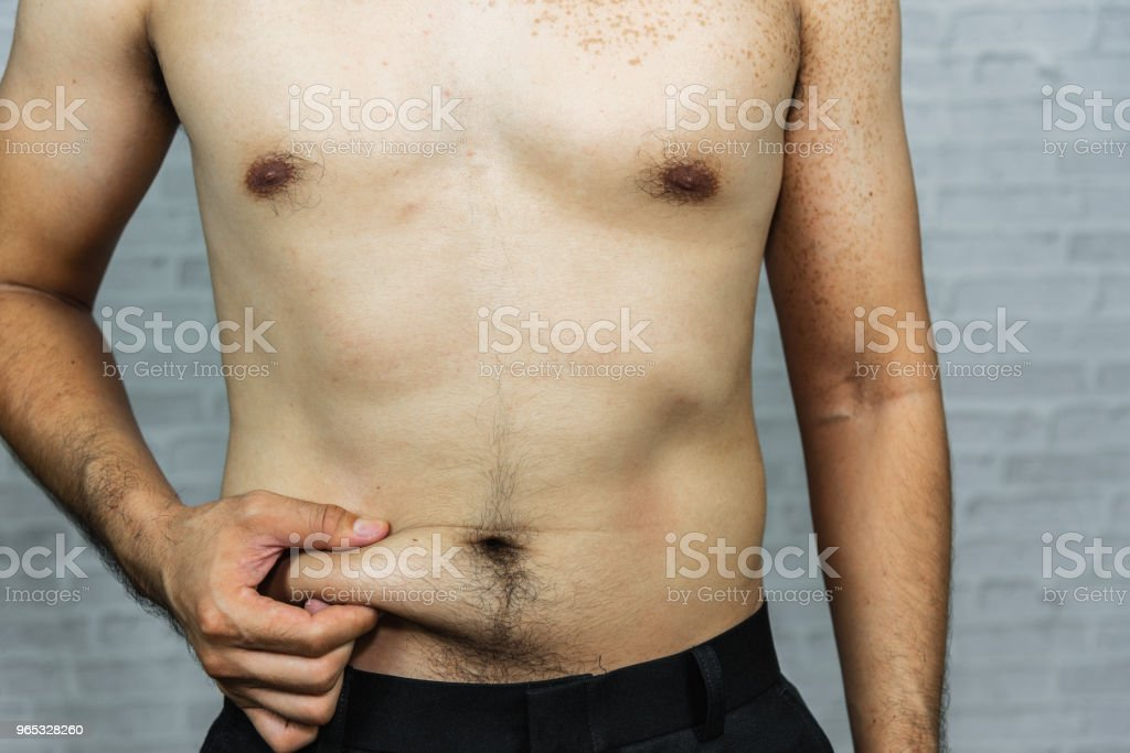 Man touching his fat belly on gray background royalty-free stock photo