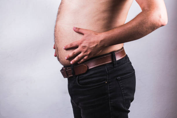 Man touching his fat belly on white background - Man fat overweight show belly stock photo