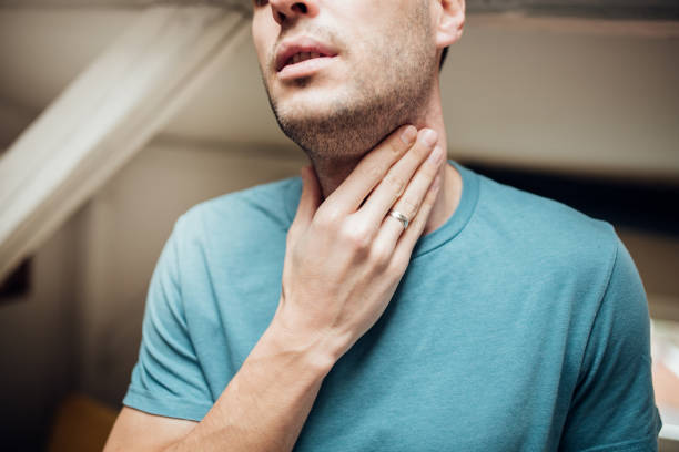 Man touching his throat Young man with a sore throat throat stock pictures, royalty-free photos & images