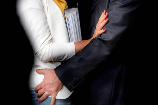 Hombre a extremo tocando mujer - acoso sexual en oficina - foto de stock