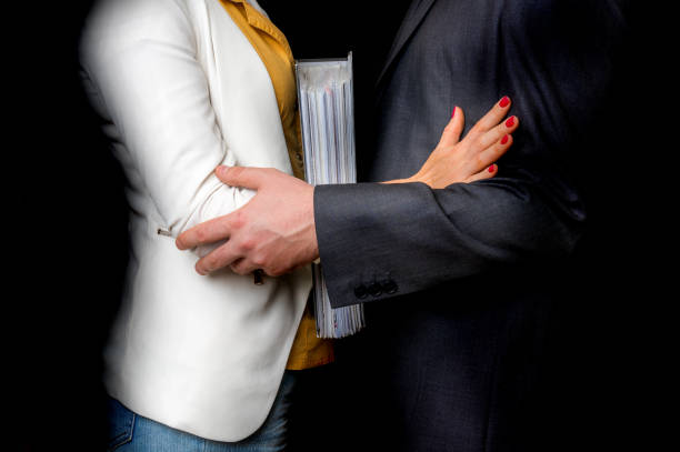 Man touching woman's elbow - sexual harassment in office stock photo
