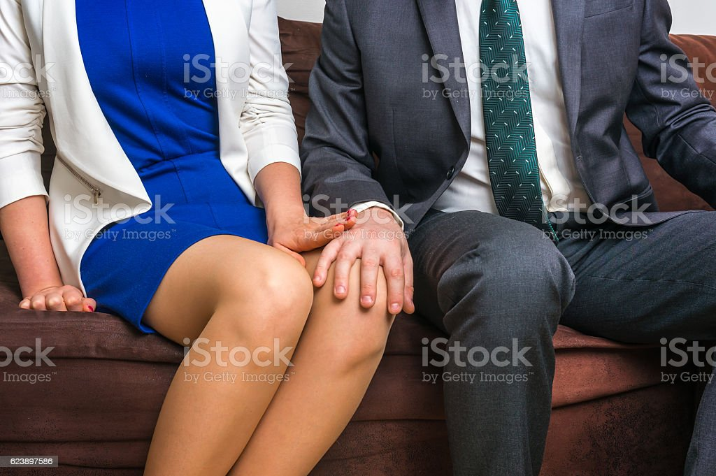 Man touching woman's knee - sexual harassment in office - foto stock