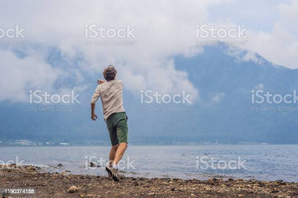 Photo of Man tourist at the lake Bratan and the mountains covered with clouds